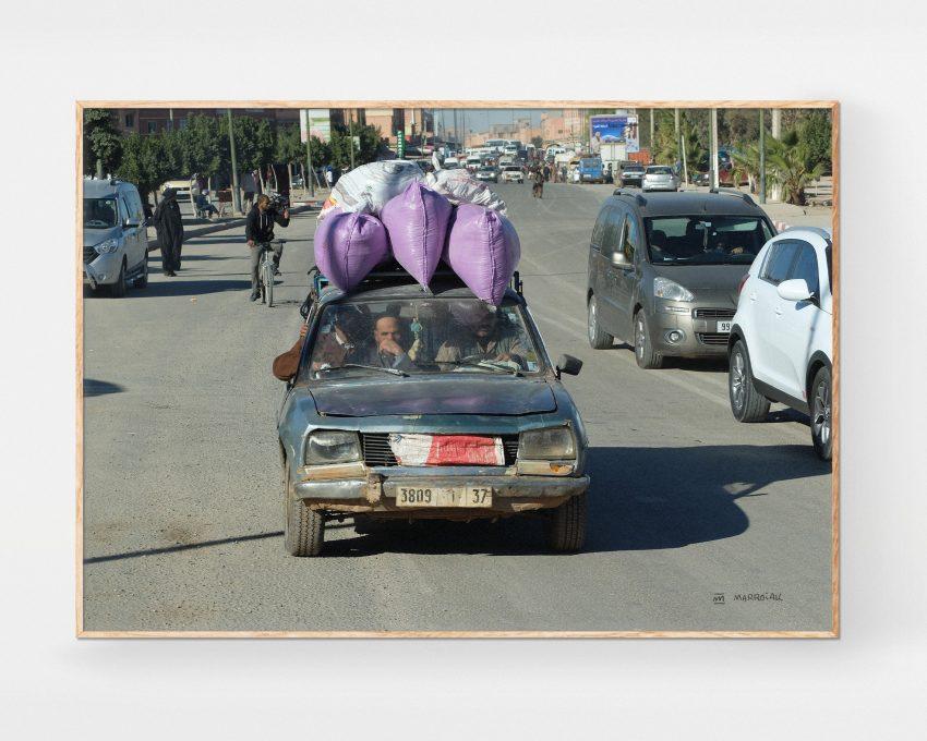 Foto enmarcada en color de un choche muy cargado y viejo en una carretera de marruecos. Venta online