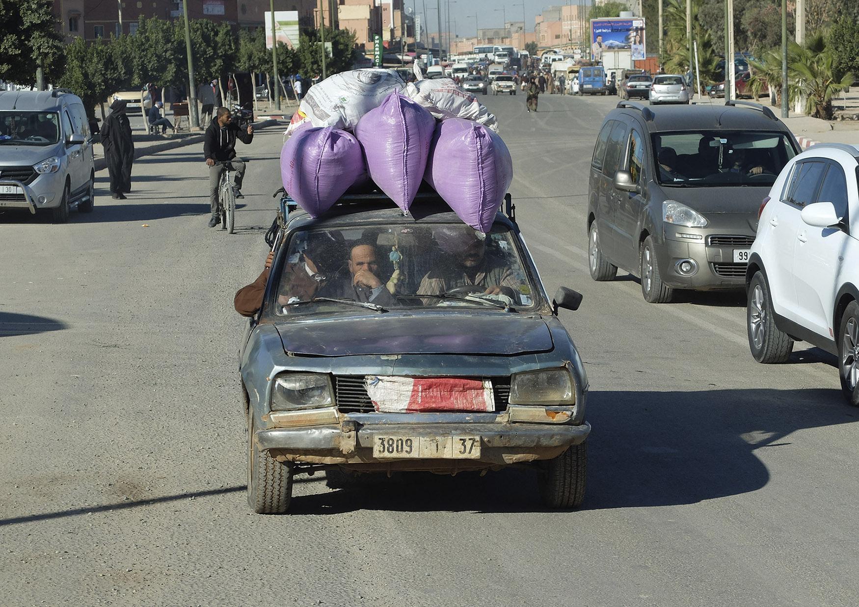 Foto en color de un choche muy cargado y viejo en una carretera de marruecos. Venta online