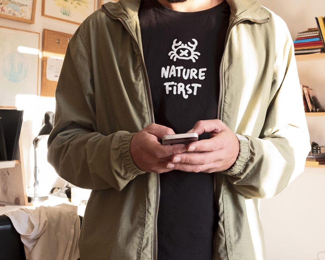 Fotografía de una camiseta negra nature first en el estudio del artista