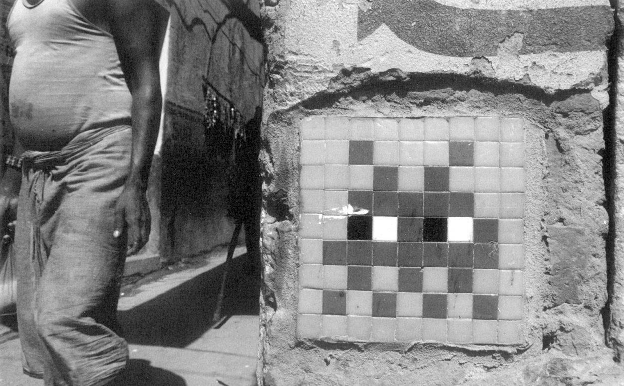 Fotografía en blanco y negro de un mosaico de Space Invaders en Varanasi, India